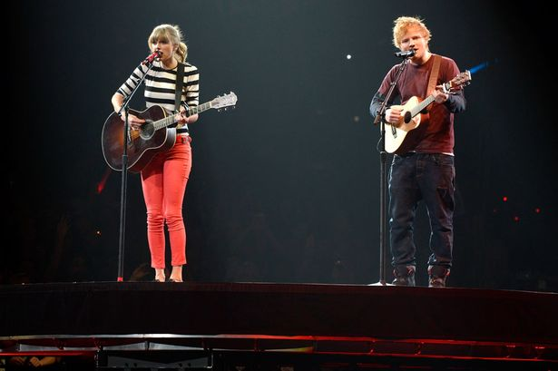 """Taylor Swift and Ed Sheeran performing """"Everything Has Changed"""" together on her 2013 Red Tour. Both artists are playing acoustic guitars as they sing."""